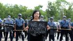 "A woman holds a sign reading ""We are Michael Brown"" in Ferguson amid police presence. Photo Credit David Broome, UPI"