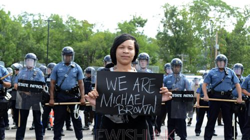 """A woman holds a sign reading """"We are Michael Brown"""" in Ferguson amid police presence. Photo Credit David Broome, UPI"""